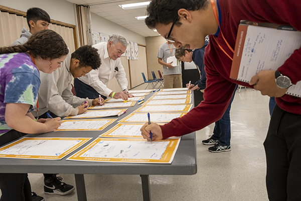 Key Leader attendees and Kiwanis International President Daniel Vigneron write personal messages for one another.