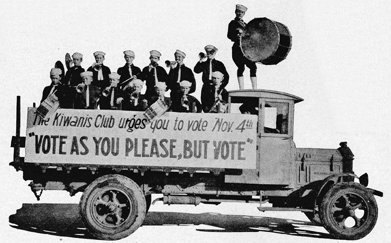 "A truck, loaded with young musicians, is decorated with a sign that reads: ""Vote as you please, but vote."""