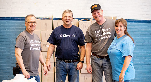 Four Kiwanis members wearing Kiwanis-branded shirts, standing in front of boxes.
