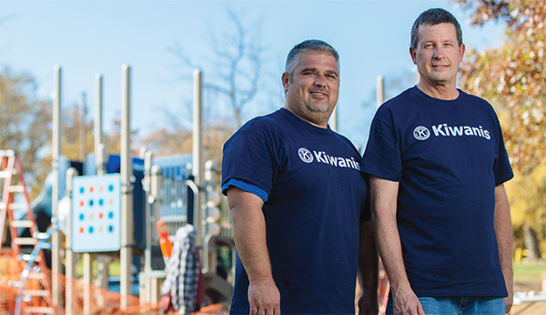 Two men, dressed in Kiwanis-branded shirts, pose at a playground-build site.