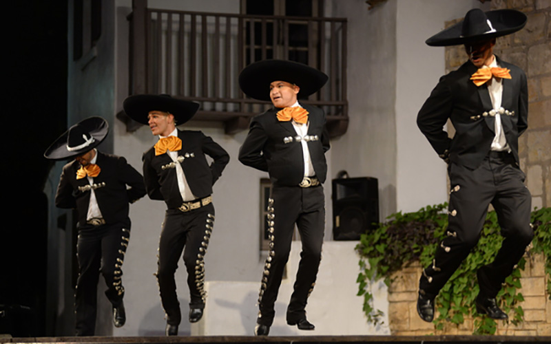 Dancers leap during a Fiesta Noche del Rio performance. Photo by Carlos Javier Sanchez