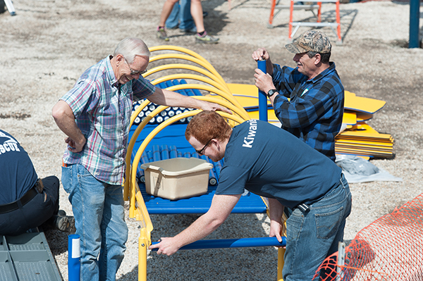 Three men assemble a piece of playground equipment.