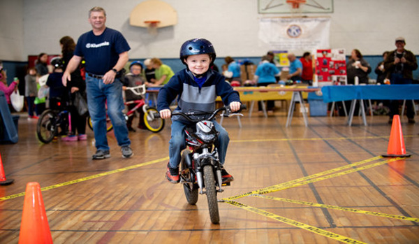 Child rides a bicycle at the Berlin, New Hampshire, Kiwanis Club safety rodeo.