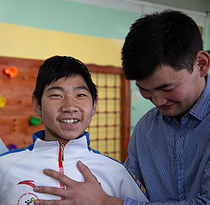 A Ulaanbaatar Vocational Training School #55 student smiles as he stands erect, fitted with prostheses that straighten his legs.