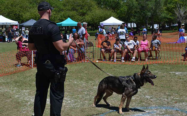 A police officer and police dog demonstrate their skills at a Florida Kiwanis club's fundraiser.