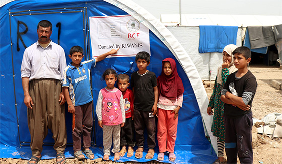 A Syrian family poses outside their new Kiwanis-donated home in Iraq.