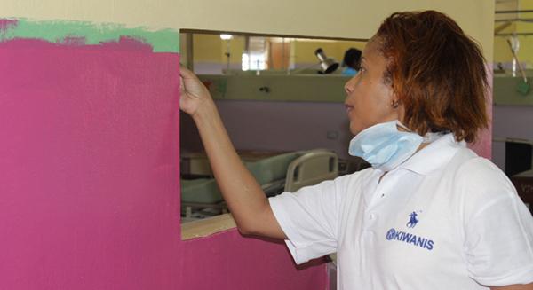 A Kiwanis volunteer paints a wall of a hospital's maternity ward.