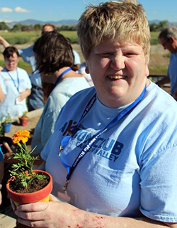 An Aktion Club member shows off a potted flower.