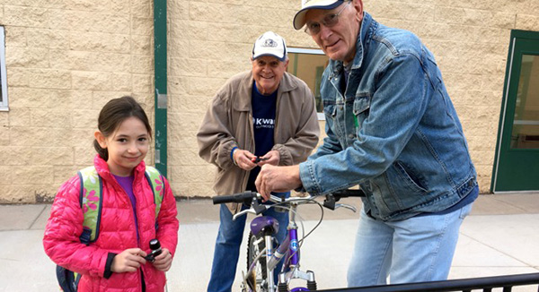 Kiwanis members help a young cyclist.