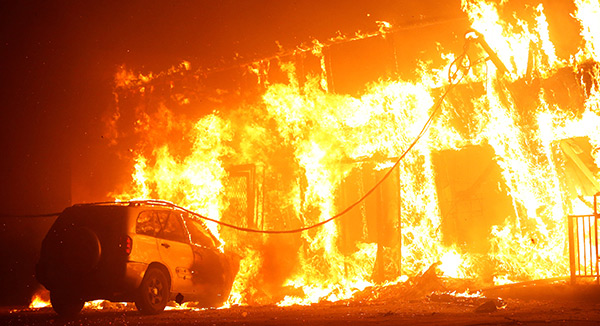Flames engulf a structure and vehicle during the 2018 Camp Fire in Paradise, California.