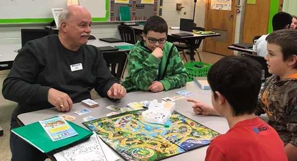 Lindberg Elementary School students and Kiwanis members play board games together.