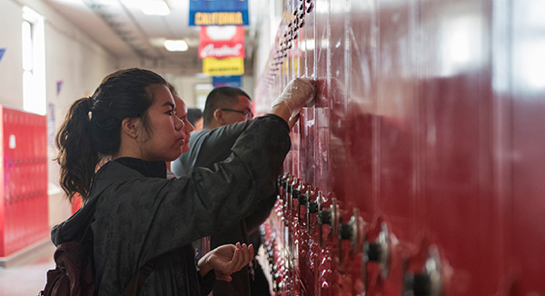 Krystene Carreon of California State University-Sacramento cleans school lockers.