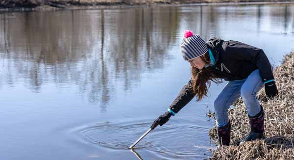 A volunteer stretches to snag a piece of trash from the Fox River.