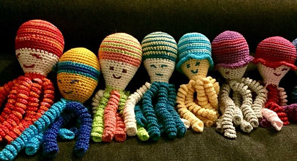 A row of crocheted octopi display a colorful selection.