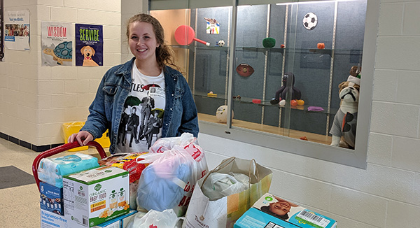 A volunteer poses with items collected for the Kiwanis Kids Closet.