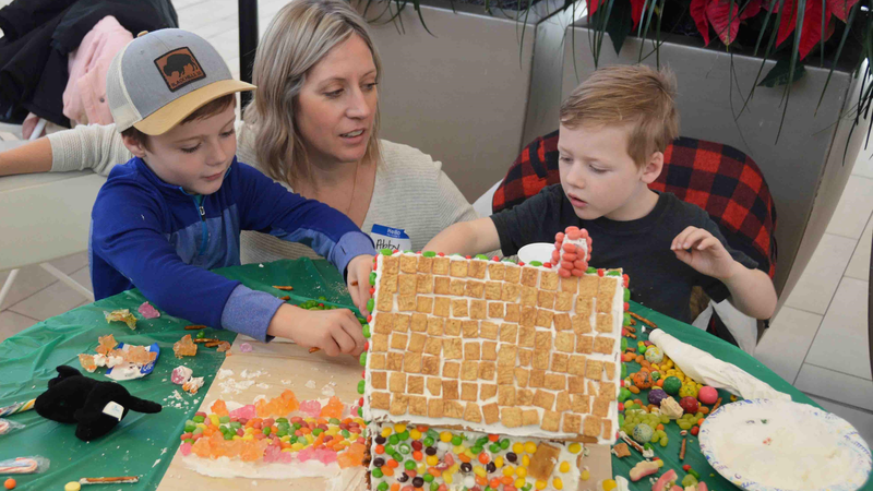 family_decorating_gingerbread_house