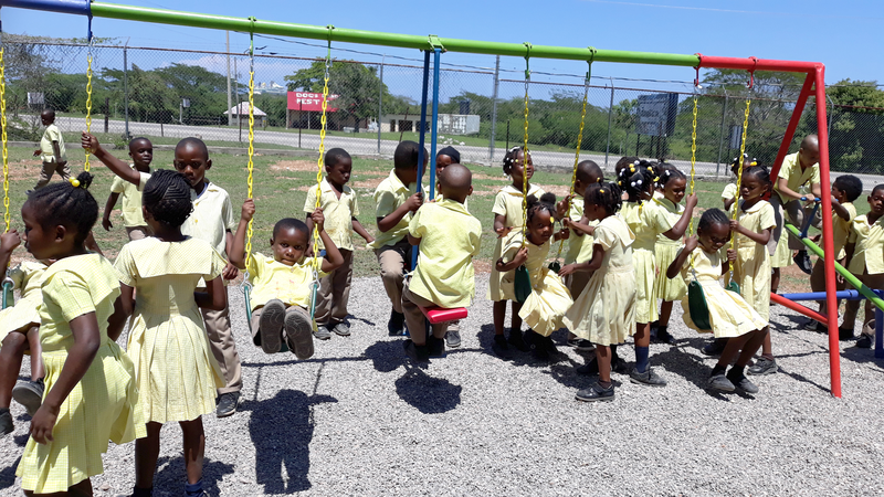 Children in Jamaica enjoy a new playground built for them by local Kiwanis clubs.